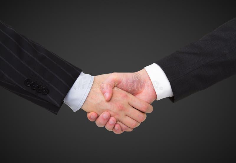 Handshake. On a black background stock photography