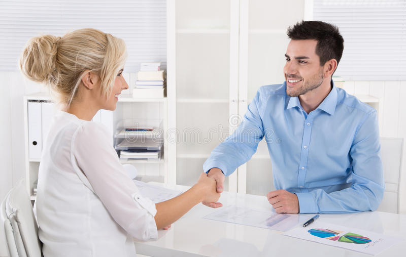 Handshake: Adviser says hello to his female customer. Handshake: Adviser says hello to his female customer sitting at desk royalty free stock photos