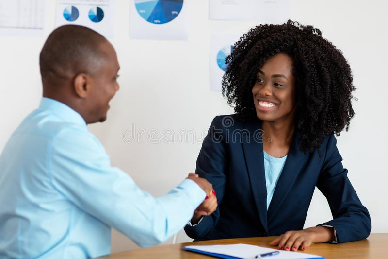Handshake of african american businesswoman with businessman after job interview royalty free stock photos