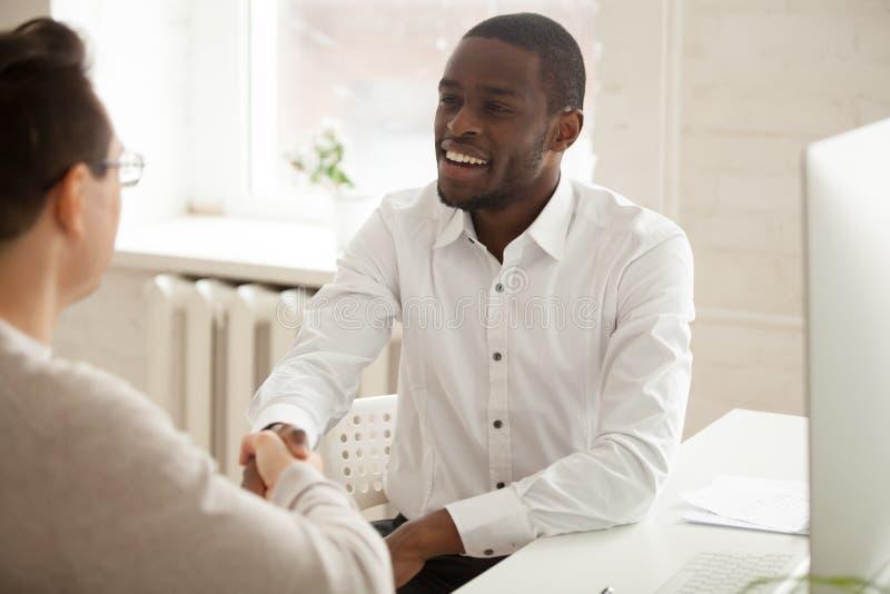 Handshake afroamericano attraente sorridente dell'uomo d'affari nuovo fotografie stock libere da diritti