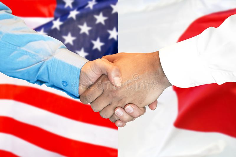 Handshake on american and Japanese flag background royalty free stock photography