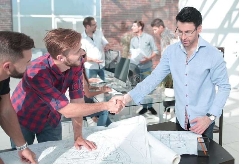 Handshake of the architect and contractor over a work Des royalty free stock photo