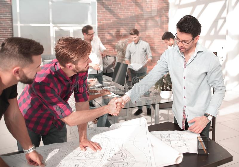 Handshake of the architect and contractor over a work Des stock images