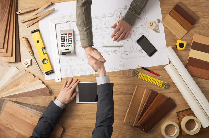 Handshake. Architect and customer businessman shaking hands top view, desktop with building project, tools and wood swatches on background stock photos