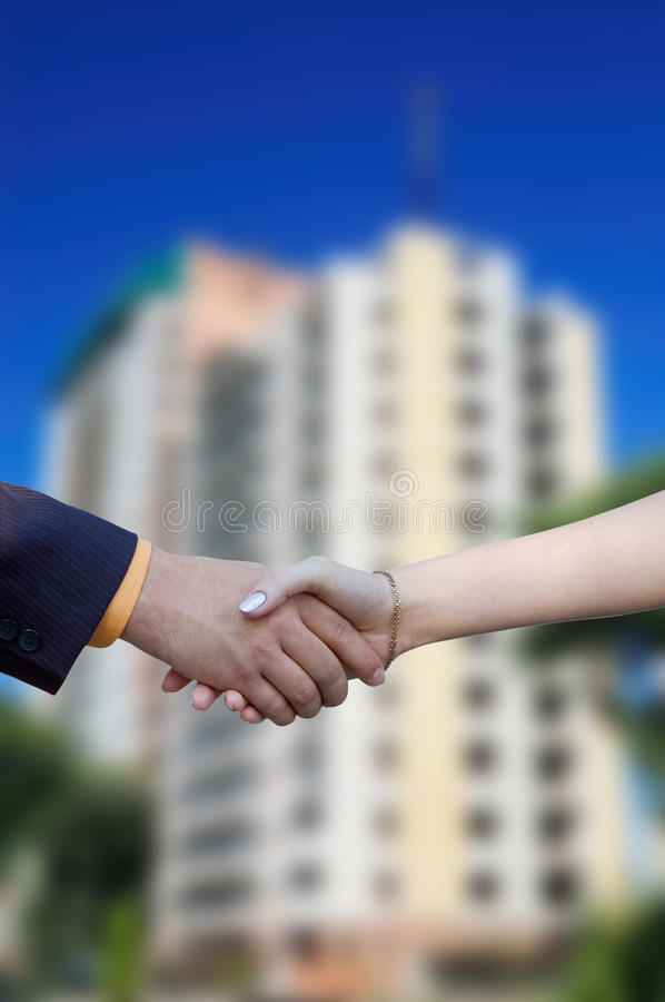 Handshake on the background of a new home royalty free stock image
