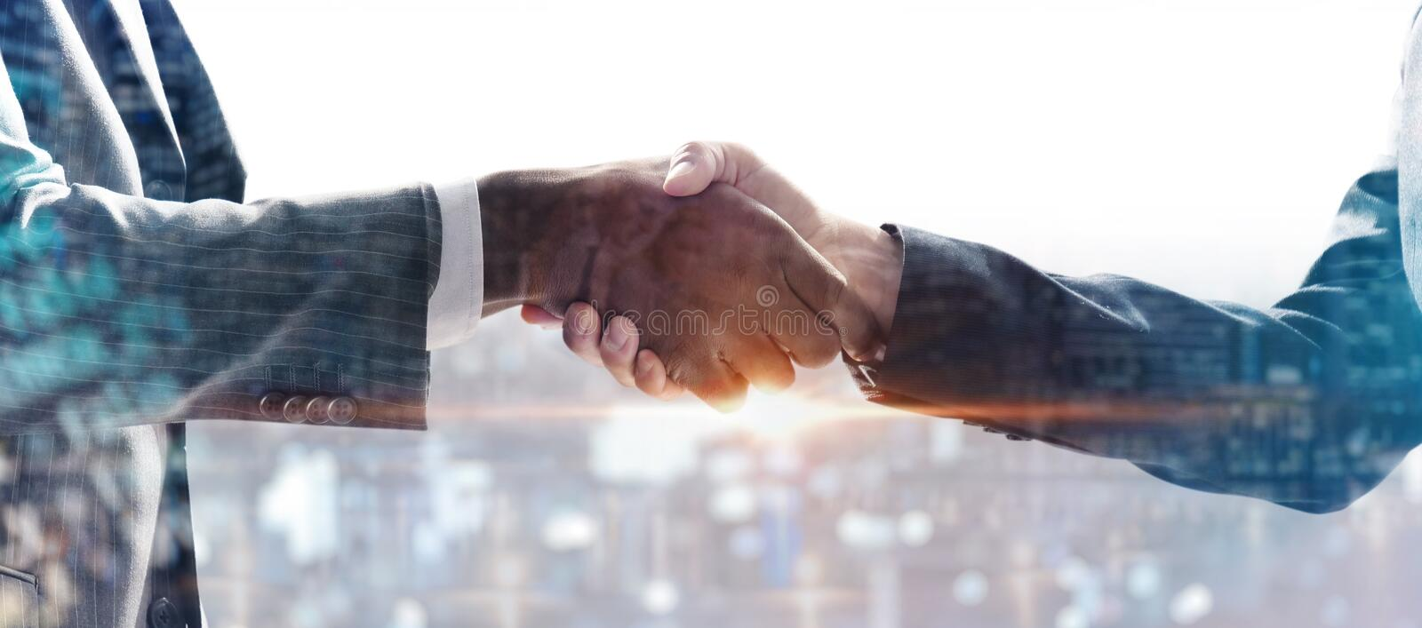 Handshake between builder edilee and engineer behind the city under construction. concept of future and work and passion for busin royalty free stock photos