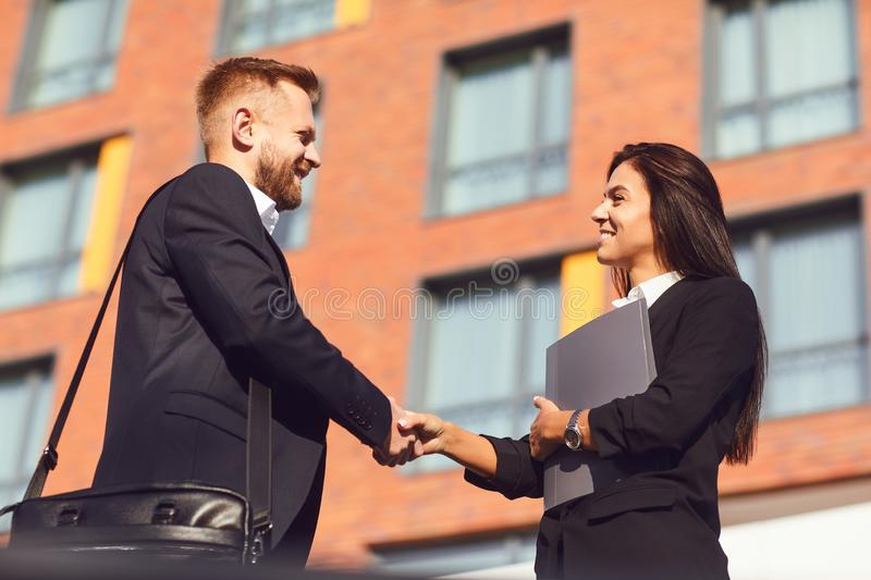Handshake business. Businessman and business woman make handshakes. Handshake business. Businessman and business women make handshakes while standing outdoors at stock photography
