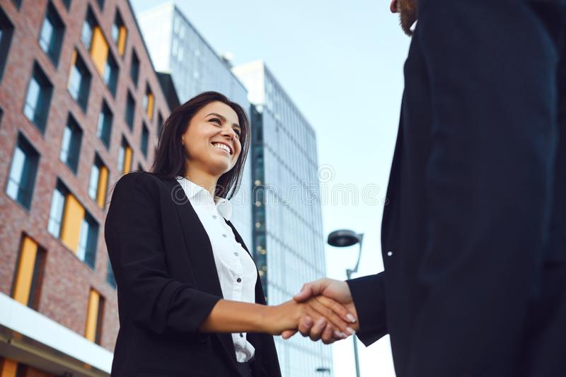 Handshake business. Businessman and business woman make handshakes while standing outdoors. Handshake business. Businessman and business women make handshakes royalty free stock photography