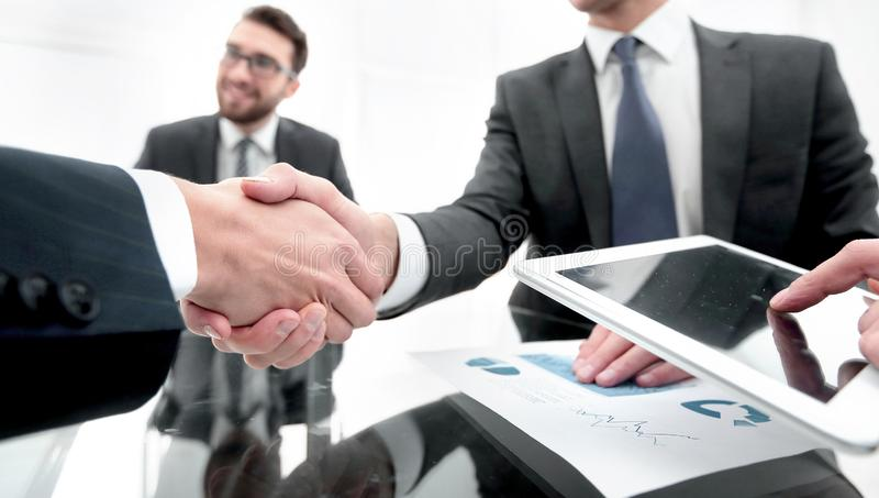 New technologies and business partnership. Handshake business colleagues in office royalty free stock photography