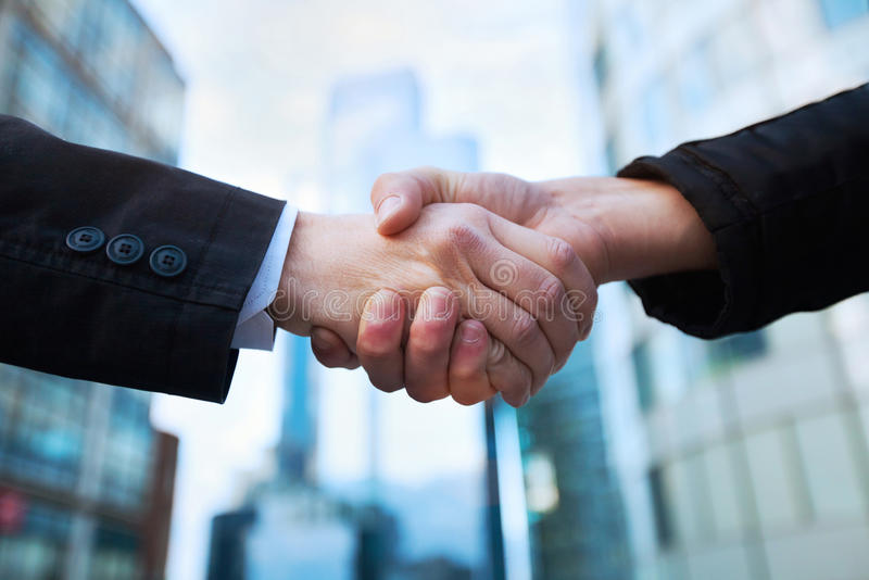 Handshake. Business concept on office buildings background