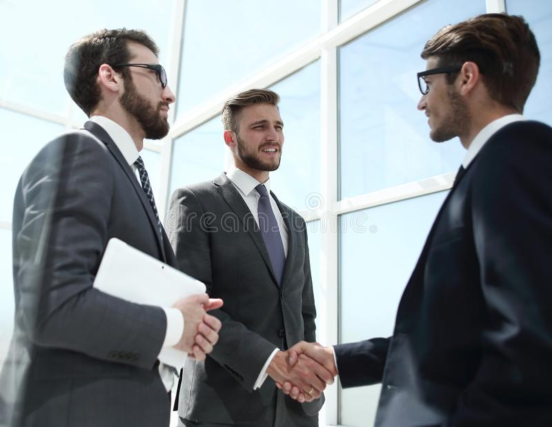 Handshake business partners behind the glass wall royalty free stock images