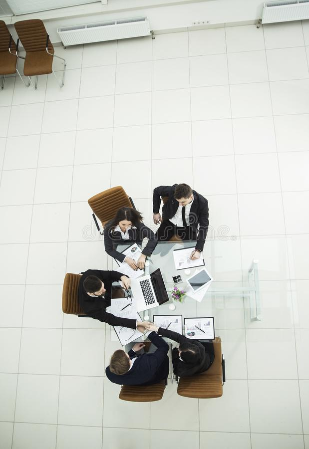 Handshake of business partners at a business meeting at the workplace. Top view - handshake of business partners at a business meeting at the workplace in the stock photos