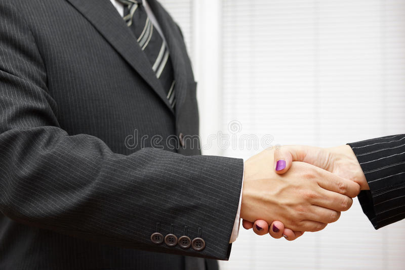 Handshake of business partners, man and woman in the office stock images