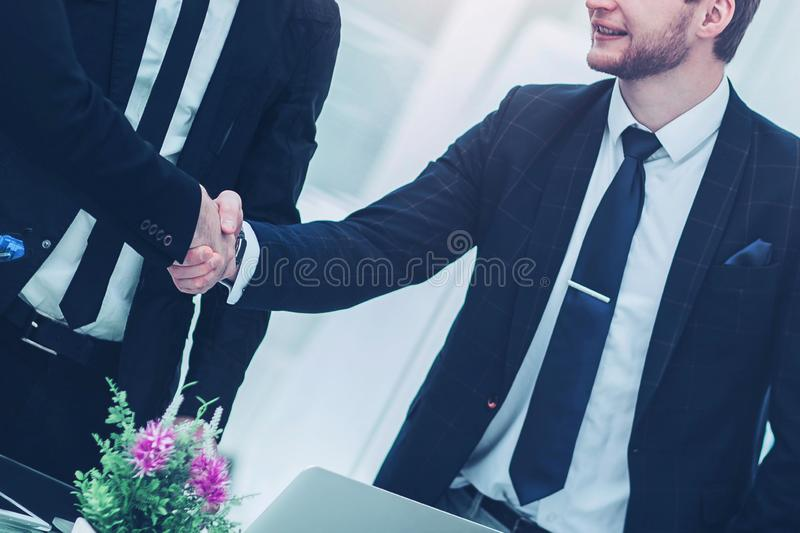 Handshake of business partners after signing the contract in the. Closeup of a successful handshake business partners after signing the contract in the workplace royalty free stock images