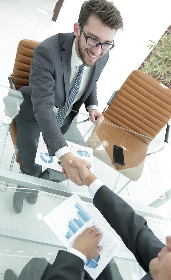 Handshake business partners at your Desk. Handshake business partners after discussion of the financial plan stock image