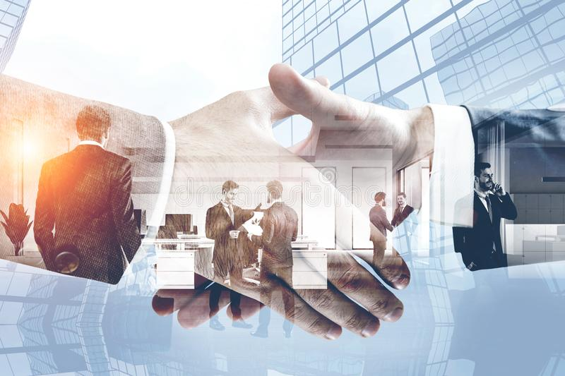 Handshake, business partnership and teamwork. Close up of two businessmen shaking hands in city with double exposure of diverse business team in office. Concept stock image