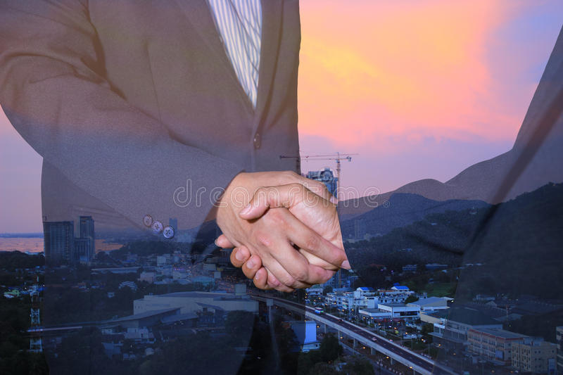 Handshake and business people concepts. Two men shaking hands on city background. royalty free stock image