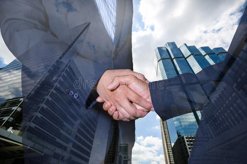 Handshake and business people concepts. Two men shaking hands on cityscape background. royalty free stock image