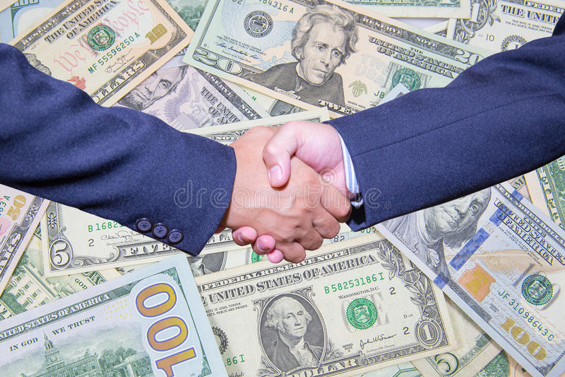 handshake and business people concepts. Two men shaking hands on Dollar Banknote background. royalty free stock images
