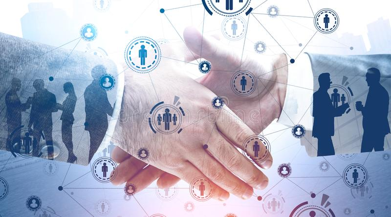 Handshake of business people, HR icons. Close up of two businessmen shaking hands over city background with double exposure of HUD social network interface and royalty free stock images