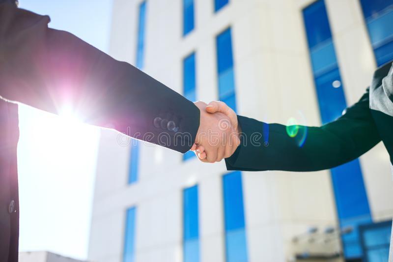 Handshake of business people over city buildings background. royalty free stock image