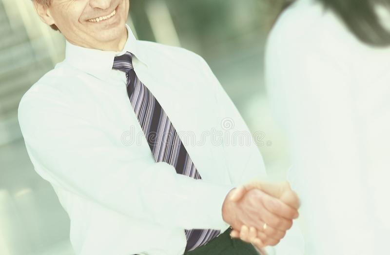 Handshake of a businessman and business women standing in the center of the modern office royalty free stock images