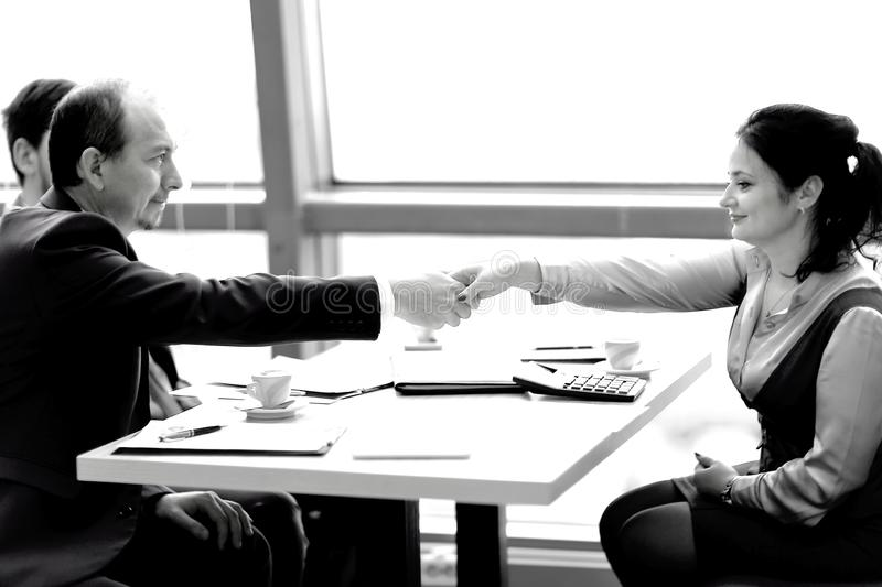 Handshake of a businessman and business woman over a Desk. royalty free stock image