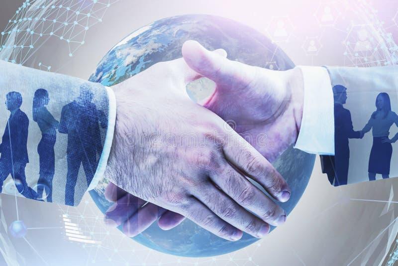 Handshake of businessmen, global social network. Handshake of two businessmen with double exposure of business people and social network hologram over planet stock images
