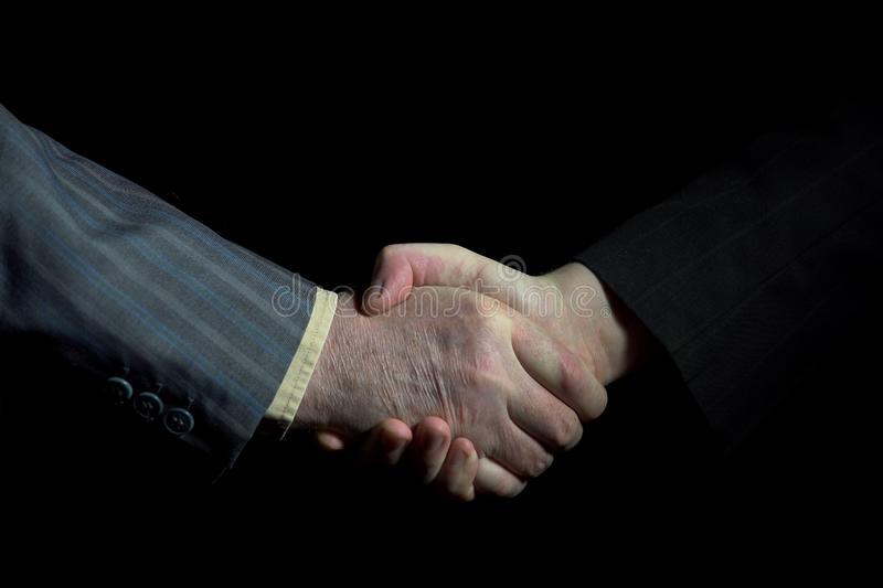 Handshake of businessmen wearing suits on a black background royalty free stock photo