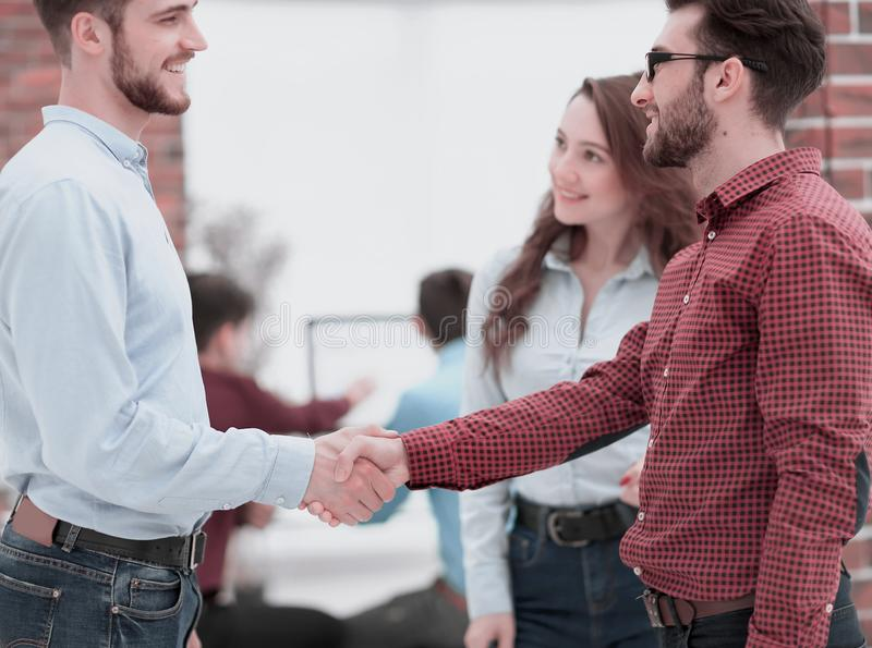Closeup image of business partners making handshake in an office. Handshake between businesspeople in a modern office royalty free stock images