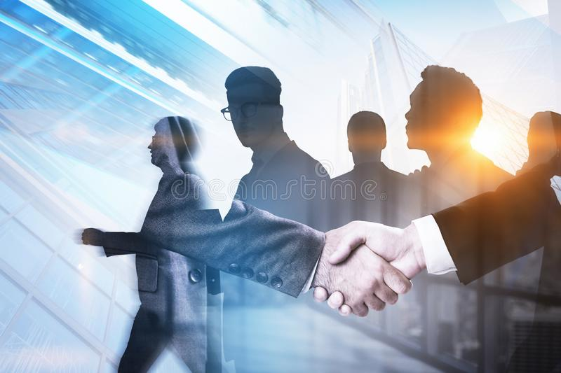 Handshake in city, business team concept. Unrecognizable businessmen shaking hands in office with double exposure of business team and cityscape background royalty free stock images