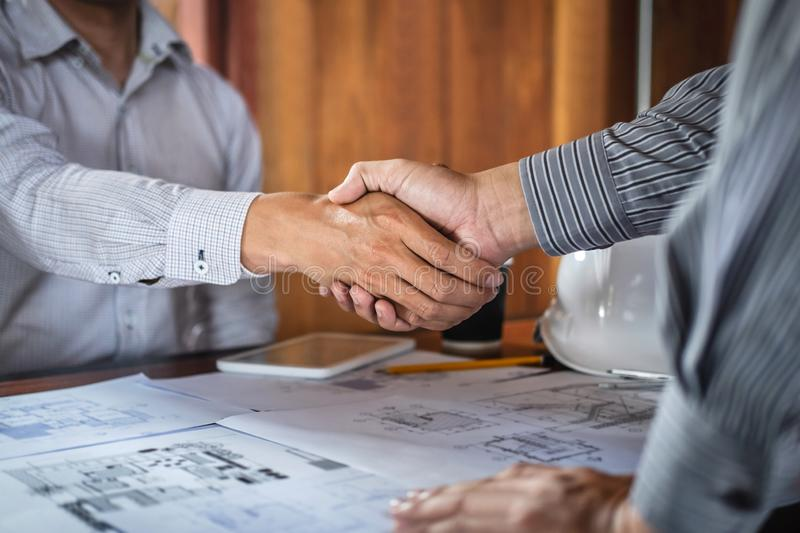 Handshake of collaboration, Construction engineering or architect discuss a blueprint and building model while checking. Information on sketching, meeting for stock photos