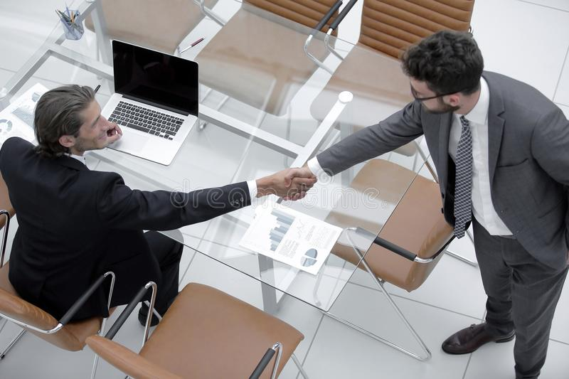 Handshake colleagues near the desktop royalty free stock image