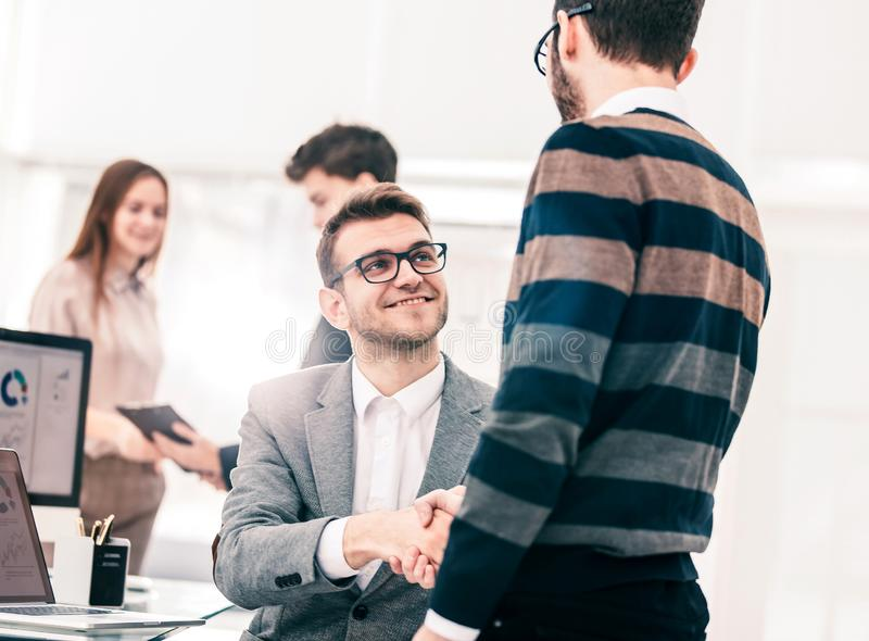 Handshake colleagues near the workplace in the modern office. stock image