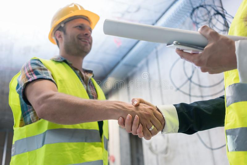 Handshake on the construction site royalty free stock photo