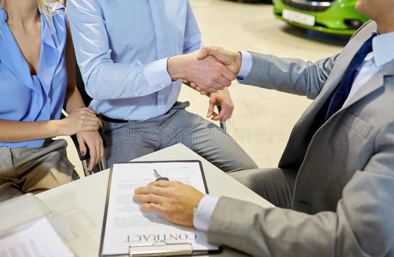 Handshake of customer and car dealer in auto salon. Auto business, car sale, gesture and people concept - close up of customers couple with dealer shaking hands stock image