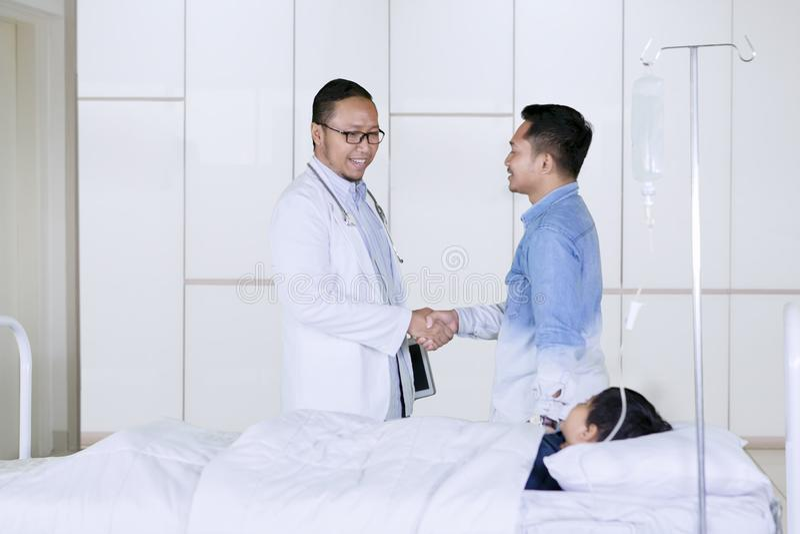 Handshake di medico con il paziente del padre in ospedale fotografia stock