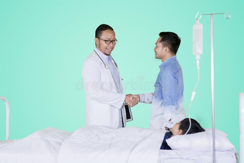Handshake di medico con il paziente del padre sullo studio fotografia stock libera da diritti