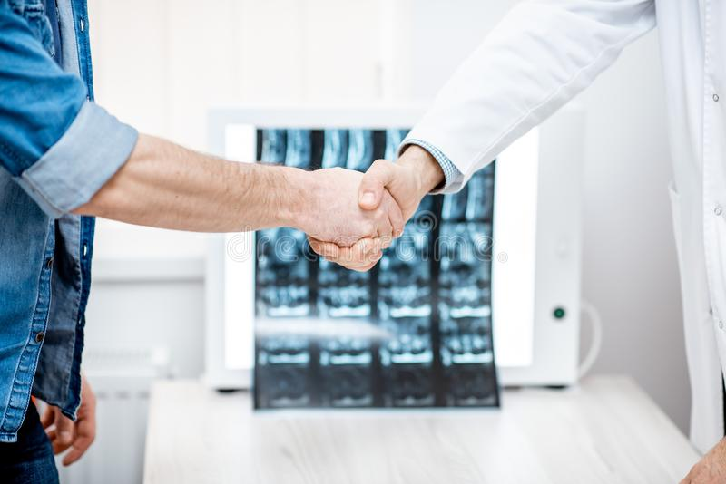 Handshake of the doctor and patient in the office. Handshake of the doctor and patient on the tomography print background at the therapist office stock photos