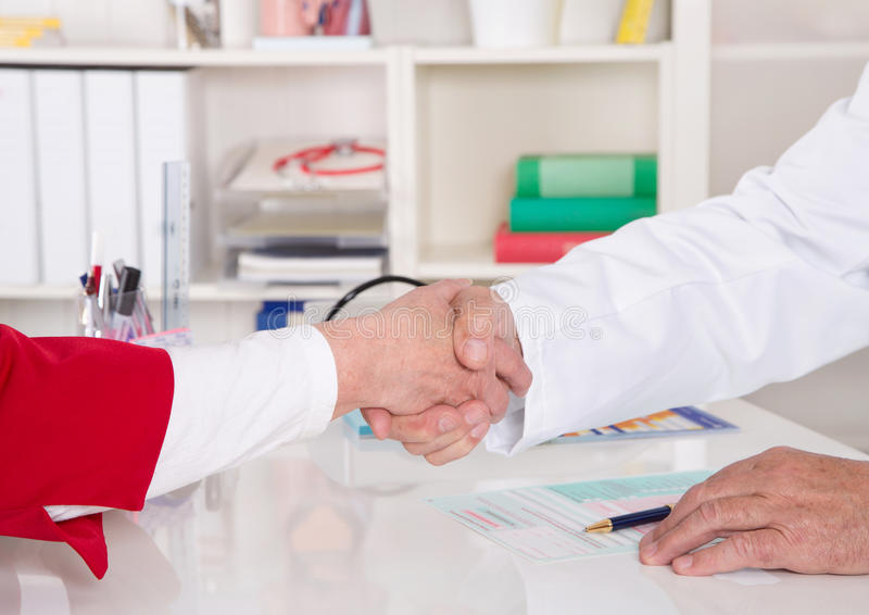 Handshake: doctor says welcome to his senior patient. royalty free stock photography