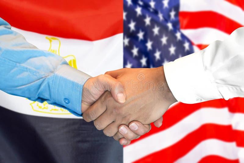 Handshake on Egypt and US flag background. Business handshake on the background of two flags. Men handshake on the background of the Egypt and United States of stock photo