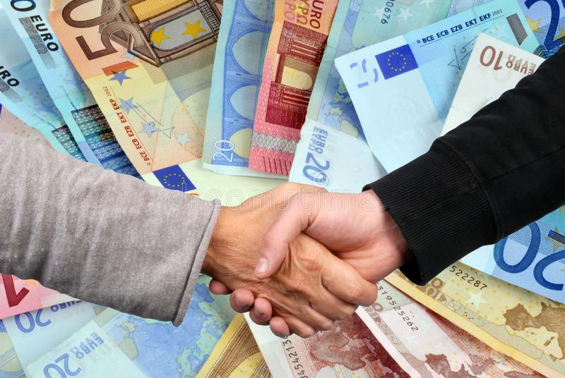 Contract concept concluded in closeup. Handshake with euro banknotes in the background stock images