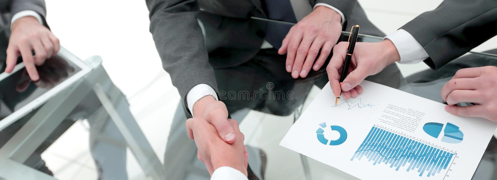 Handshake of financial partners at the Desk stock photography
