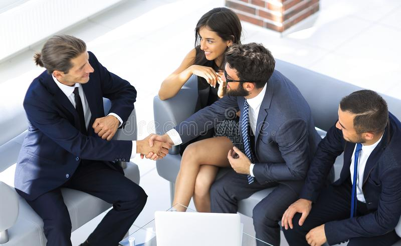Handshake Manager and the client sitting in the office lobby. In front of the open laptop royalty free stock photos