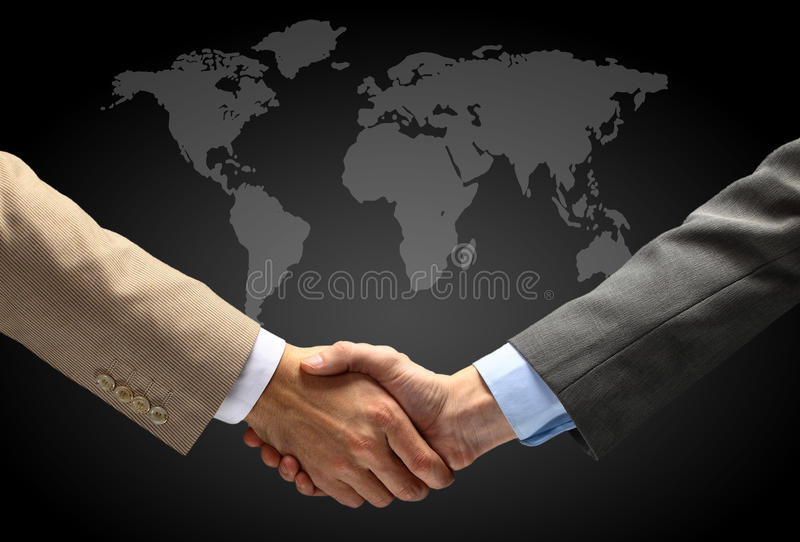 Handshake With Map Of The World Royalty Free Stock Photos