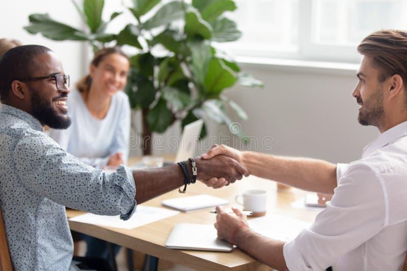 Handshake multirazziale che ringrazia, presentare degli uomini d'affari, accoglientesi fotografia stock libera da diritti