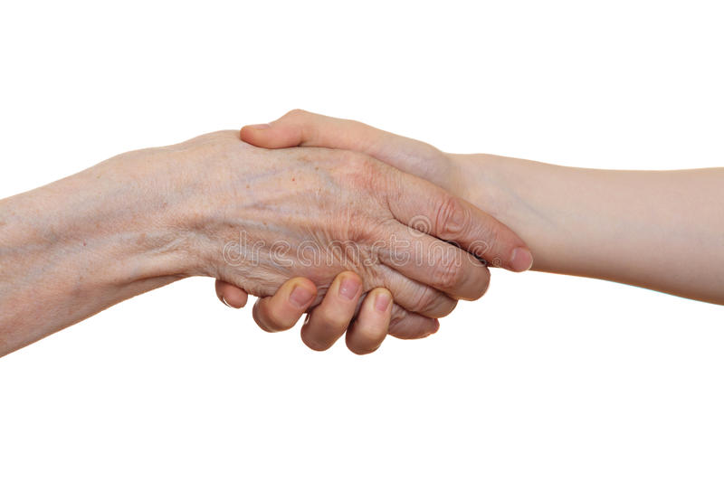 Handshake between an old person with a wrinkled hand and a kid royalty free stock images