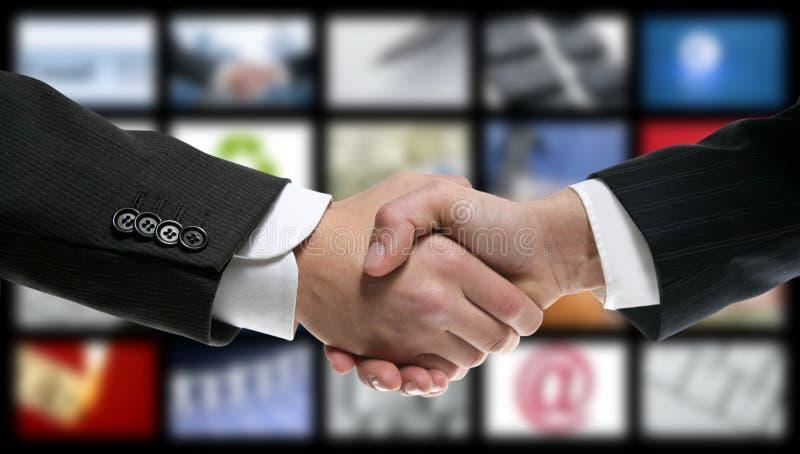 Handshake over video tv screen technology stock photography