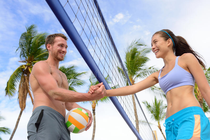 Handshake people in beach volleyball shaking hands. After volley ball game on summer beach. Man and women model living healthy active fitness lifestyle doing royalty free stock image