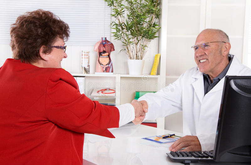 Handshake: Portrait of an older doctor with experience with patient. Medical date stock photography